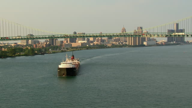 detroit, michigan - july 7, 2011: aerial view of cargo ship on detroit river with the skyline of detroit in the background. - detroit river stock-videos und b-roll-filmmaterial