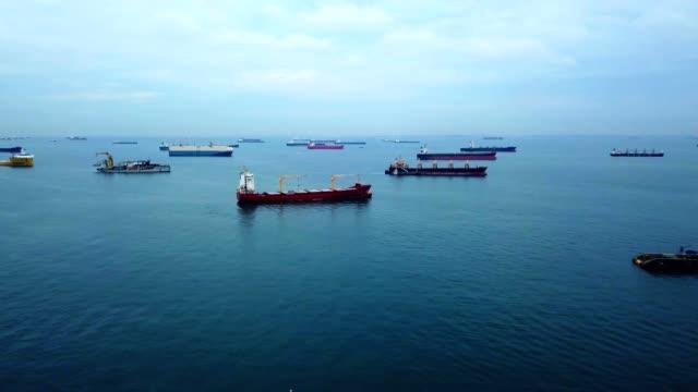 stockvideo's en b-roll-footage met luchtfoto van vrachtschepen verankerd in de zee bij singapore city - binnenschip