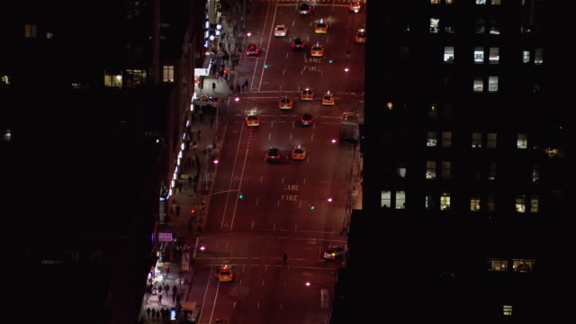Aerial view of cars moving along New York City street at night.