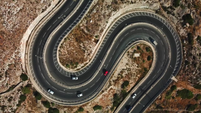 aerial view of cars on a winding road shaped as letter s - winding road stock videos & royalty-free footage