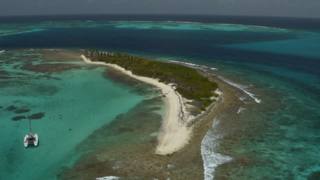 aerial view of catamaran boat floating near remote island beach / petit tabac, tobago cays, saint vincent and the grenadines - distant stock videos & royalty-free footage
