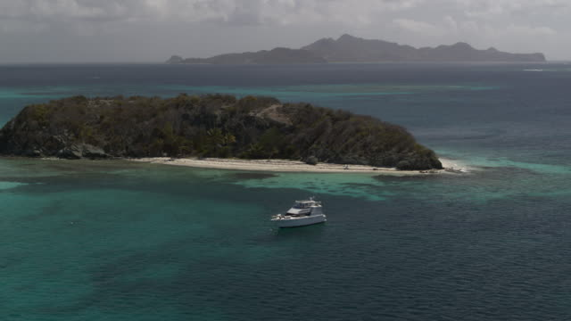 aerial view of catamaran boat floating near remote island / jamesby, saint vincent and the grenadines - distant stock videos & royalty-free footage