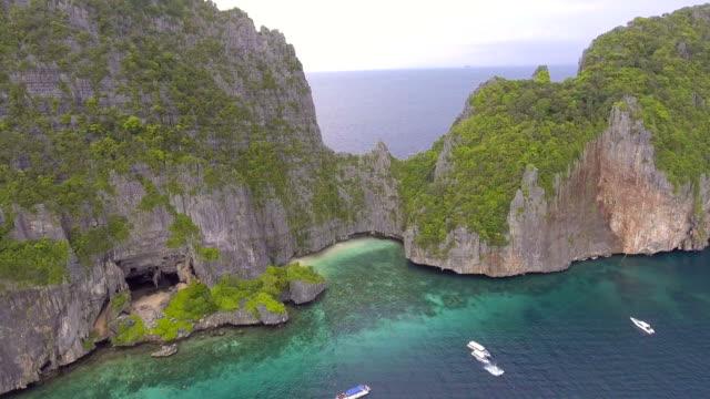 vídeos de stock e filmes b-roll de aerial view of cave and beach with beautiful cliff at phi phi island, thailand - mar de andamão