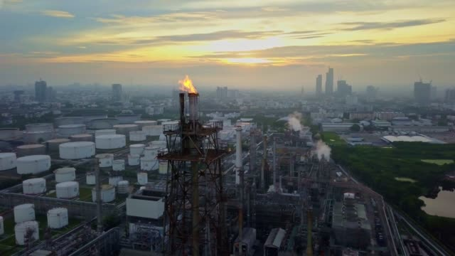 aerial view of chemical or refinery plant with burning torch at sunrise in the city - fuel pump stock videos and b-roll footage