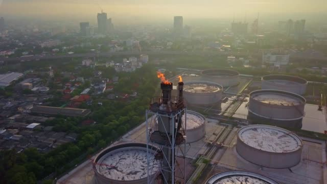 aerial view of chemical or refinery plant with burning torch, storage tank at sunrise in the city - smog stock videos & royalty-free footage
