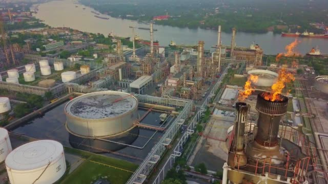 aerial view of chemical or refinery plant with burning torch, storage tank at sunrise in the city - industria petrolifera video stock e b–roll
