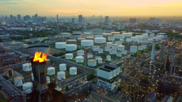 aerial view of chemical or refinery plant with burning torch, storage tank at sunrise in the city - storage tank stock videos and b-roll footage
