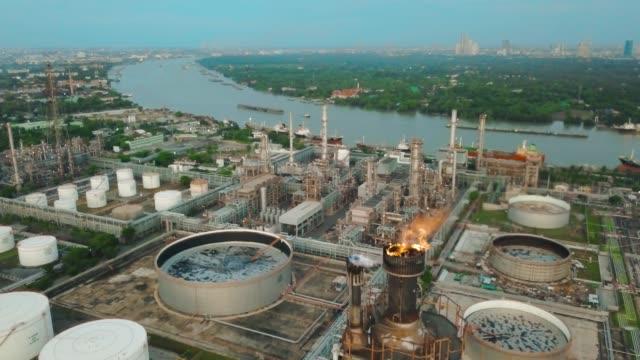 vídeos de stock, filmes e b-roll de vista aérea da planta química ou refinaria com tocha ardente, tanque de armazenamento ao nascer do sol na cidade - tanque de armazenamento