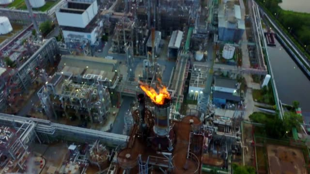 aerial view of chemical or refinery plant with burning torch, storage tank at sunrise in the city - petrol stock videos & royalty-free footage