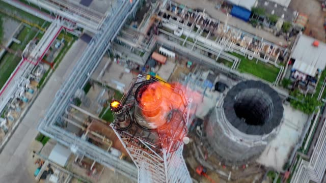 aerial view of chemical, refinery, power plant with burning torch, storage tank at sunrise near mountain and sea - flaming torch stock videos & royalty-free footage