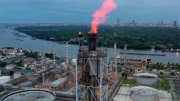 Aerial view of chemical, refinery, power plant with Burning torch, Storage tank at sunrise near mountain and sea