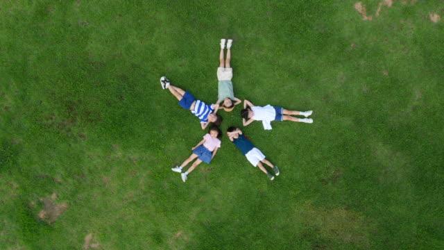 vídeos y material grabado en eventos de stock de aerial view of children lying on lawn with closed eyes in summer at seoulforest (the third largest park in seoul city) - manos detrás de la cabeza