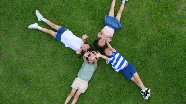aerial view of children lying on lawn with closed eyes in summer at seoulforest (the third largest park in seoul city) - legs crossed at ankle stock videos and b-roll footage