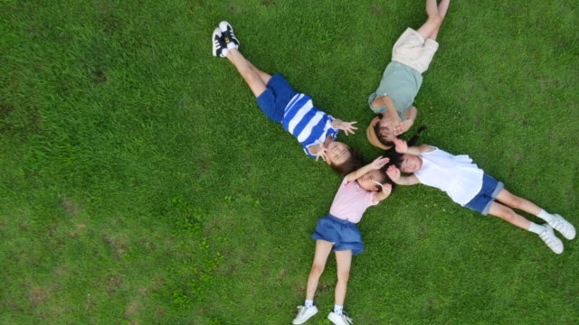 Aerial view of children lying on lawn with closed eyes in summer at Seoulforest (the third largest park in Seoul city)