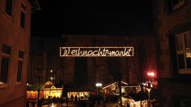 """aerial view of christmas decorations and lighting over the street with the words """"weihnachtsmarkt"""" in göttingen, germany. - christmas market stock videos & royalty-free footage"""