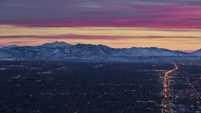vídeos de stock, filmes e b-roll de t/l aerial view of city and traffic with mountains in the background at sunset / salt lake city, utah, usa - utah