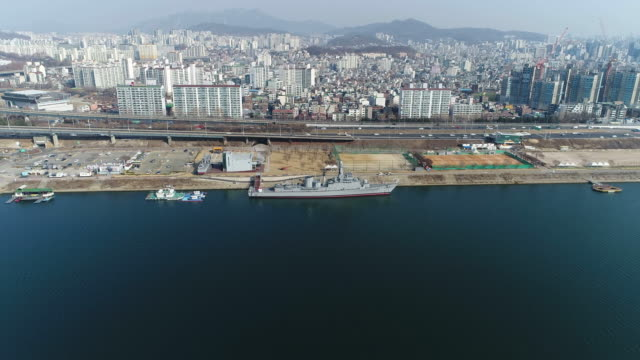 vídeos y material grabado en eventos de stock de aerial view of city around the seoul battleship park (the first shipbuilding theme park) in seoul at daytime - anclado