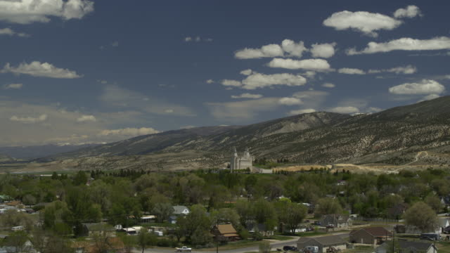 stockvideo's en b-roll-footage met aerial view of city in valley near mountains approaching temple / manti, utah, united states - valley