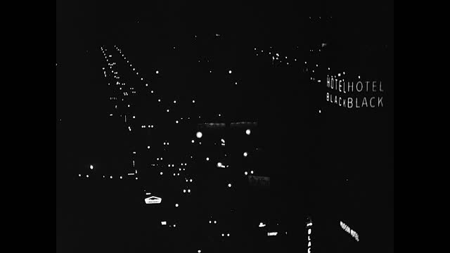 """vidéos et rushes de aerial view of citylight in the night, car headlights driving down the street and neon sign """"hotel black"""" on the right of the frame - phare de véhicule"""