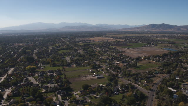 vídeos de stock, filmes e b-roll de aerial view of cityscape approaching mountains / pleasant grove, utah, united states - utah