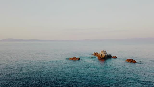 vidéos et rushes de vue aérienne des falaises dans les eaux calmes de la mer et de rivage lointain - grèce