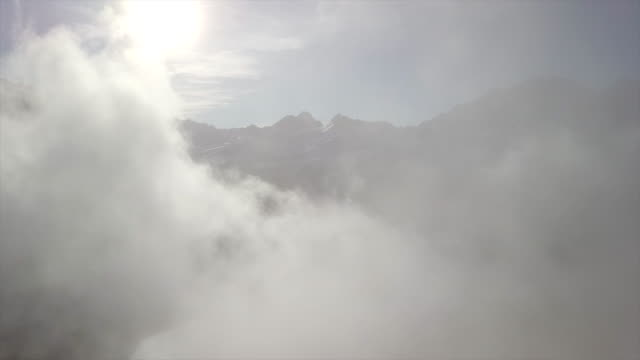 aerial view of clouds and fog in the mountains in winter. - time-lapse - land stock videos & royalty-free footage