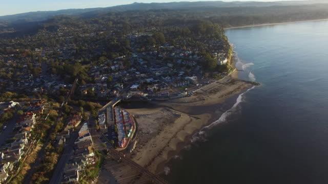 aerial view of coastal cityscape at beach during sunset, drone moving from towards buildings in city near sea - santa cruz, california - カリフォルニア州サンタクルーズ点の映像素材/bロール