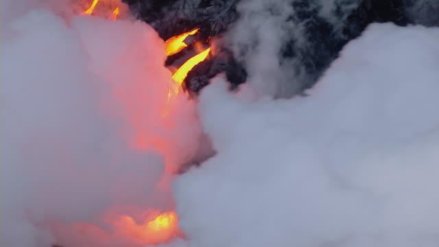 Aerial view of coastal lava flow in Hawaii Volcanoes National Park at dusk.