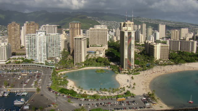vidéos et rushes de aerial view of coastal skyscrapers and duke paoa kahanamoku lagoon with distant mountains in honolulu, hawaii. - pataugeoire