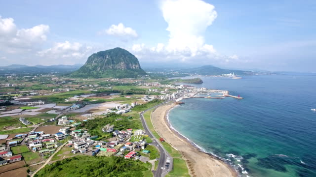Aerial view of Coastal Village with Sea of Jeju and Sanbangsan mountain in distance