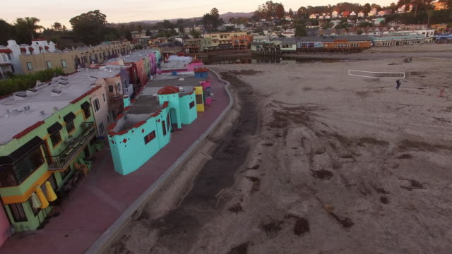 stockvideo's en b-roll-footage met aerial view of colorful buildings in city with birds over water, drone moving forward over houses at beach during sunset - santa cruz, california - santa cruz californië