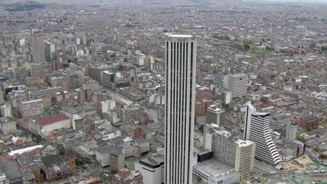 aerial view of colpatria tower with crowded cityscape in bogota, colombia - ヘリポート点の映像素材/bロール