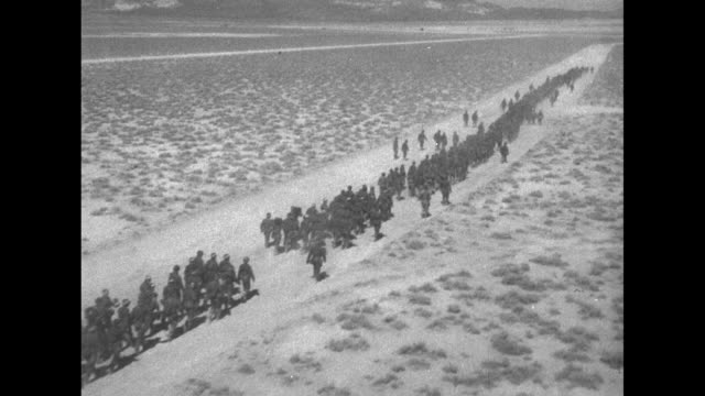 stockvideo's en b-roll-footage met aerial view of columns of us army soldiers marching along desert road / vs soldiers climb down into trench / vs soldiers in trench / note exact day... - massavernietigingswapens