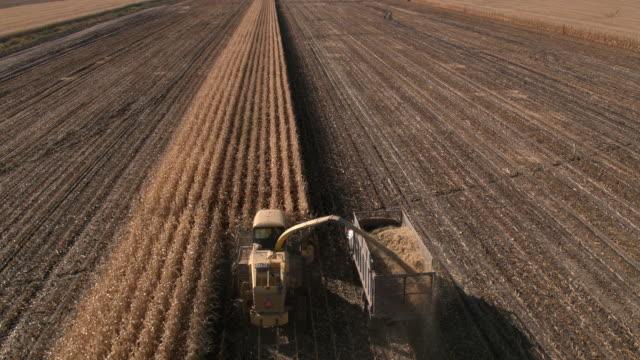 aerial view of combine loading truck in cornfield - コンバイン点の映像素材/bロール
