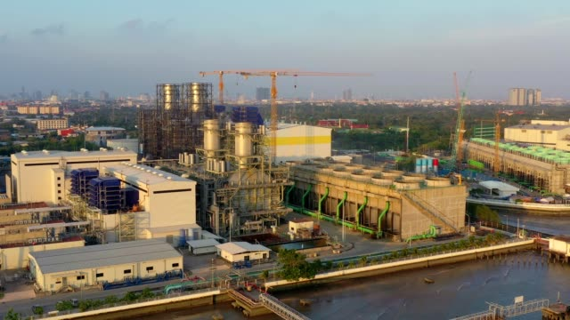 aerial view of combined cycle power plant and cooling tower at sunset - synthpop stock videos & royalty-free footage
