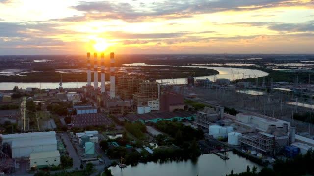stockvideo's en b-roll-footage met luchtfoto van de gecombineerde cyclus krachtcentrale en thermische power plant met pluim of stoom in koeltoren bij zonsondergang - warmwaterbron