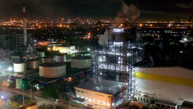vídeos de stock e filmes b-roll de aerial view of combined cycle power plant or fuel gas powerplant with plume or steam at cooling tower at night - central elétrica