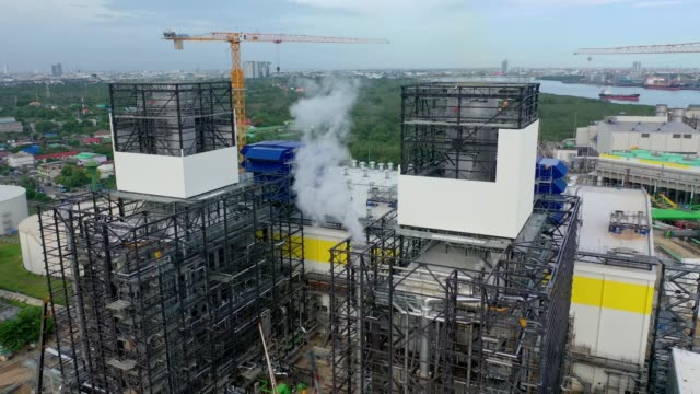 aerial view of combined cycle power plant or fuel gas powerplant with plume or steam at cooling tower - synthpop stock videos & royalty-free footage