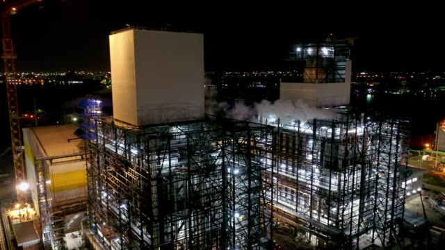 aerial view of combined cycle power plant or fuel gas powerplant with plume or steam at cooling tower at night - synthpop stock videos & royalty-free footage