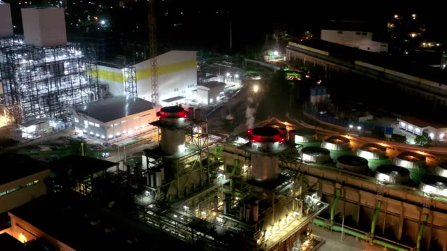 aerial view of combined cycle power plant or fuel gas powerplant with plume or steam at cooling tower at night - cooling tower stock videos & royalty-free footage