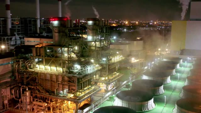aerial view of combined cycle power plant or fuel gas powerplant with cooling tower and plume or steam at cooling tower or steam at night - power station stock videos & royalty-free footage