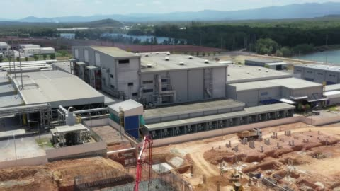 aerial view of construction machinery and material on the construction site of a huge warehouse - crane construction machinery stock videos & royalty-free footage
