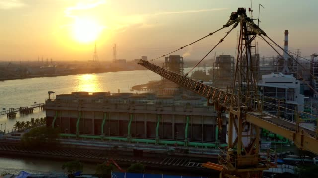 aerial view of construction site with tower crane of combined cycle power plant and cooling tower at sunset - synthpop stock videos & royalty-free footage