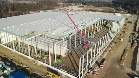 aerial view of construction workers laying the roof on a masive distribution warehouse - crane construction machinery stock videos & royalty-free footage