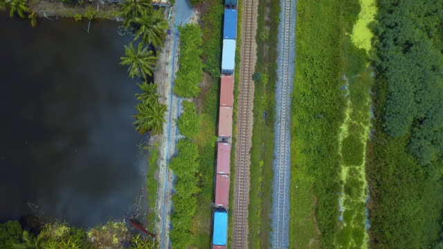 aerial view of container freight train transporting goods across the country - railway track stock videos & royalty-free footage