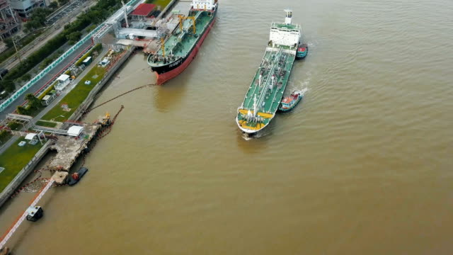 aerial view of container ship and oil refinery near river - unloading stock videos & royalty-free footage