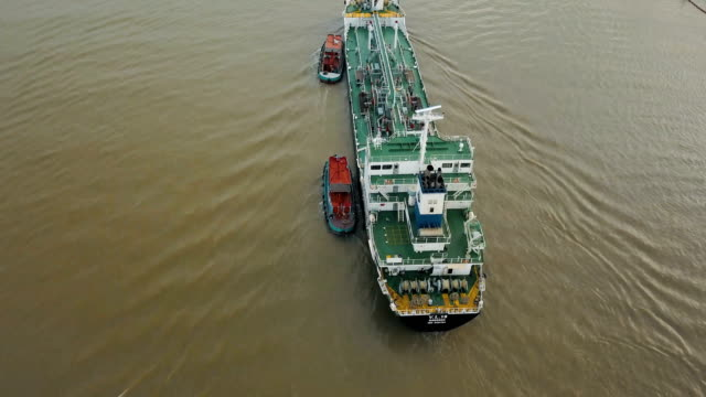 Aerial view of container ship and oil refinery near river