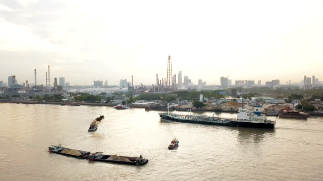 aerial view of container ship and oil refinery near river - film container stock videos & royalty-free footage