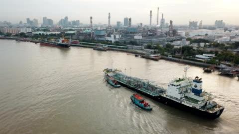 stockvideo's en b-roll-footage met luchtfoto van het containerschip en olieraffinaderij in de buurt van rivier - merchandise