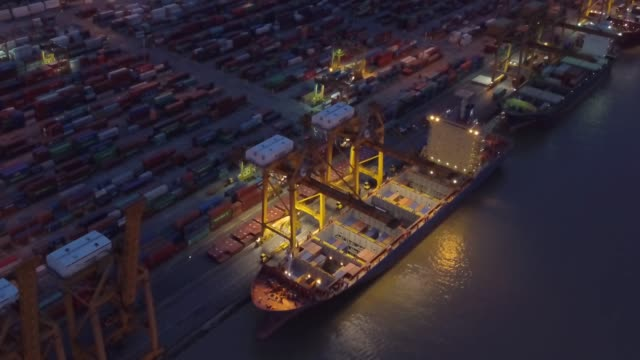 aerial view of container ship in the harbor at night shot. cloudy sky. - cargo ship stock videos & royalty-free footage
